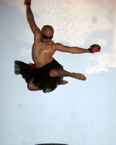 A shirtless man leaping in the air with a sky-blue background