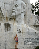 Photo: Claire Dillon stands in front of a bas relief image of Lenin in Lenin Park, Havana, Cuba